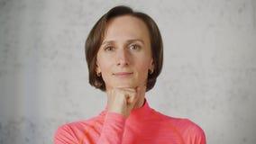 Menton de participation de femme adulte de portrait dans le poing regardant à la caméra Femme de brune faisant l'imitateur facial clips vidéos