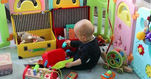 Young baby boy playing with his toys in playpen stock footage