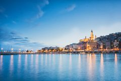 Menton stad på natten, franska Riviera, blått timmesolnedgånglynne arkivfoto