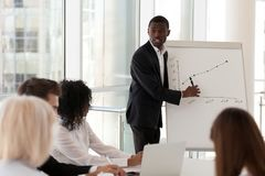 Mentor afro-americano sério que dá a apresentação que explica s foto de stock