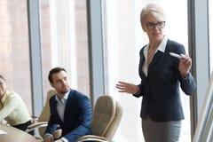 Mentor de meia idade seguro que fala dando a apresentação no treinamento executivo da equipe imagem de stock royalty free