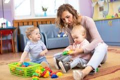Mentor et bébés de 1 années jouant avec les jouets éducatifs dans le jardin d'enfants photographie stock libre de droits