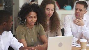 Mentor fêmea africano para ensinar empregados diversos explicar o trabalho do computador video estoque