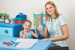 Mentor and five-year girl joyfully show the thumbs up by doing a regular job Stock Photos