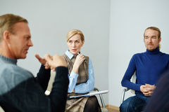 Mentor Helping People in Group Therapy. Portrait of mature professional psychologist giving guidance to mental health patients, listening to their problems in stock images