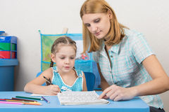 Mentor shows five children to write letters correctly Stock Photo