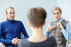 Mentor Talking to Patient in Group Meeting. Portrait of mature women talking to patient in group therapy meeting, consulting about mental health issues stock image