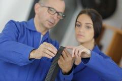 Mentor teaching female apprentice. Female stock image