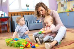 Mentor and 1 years old babies playing with educational toys in kindergarten royalty free stock photography