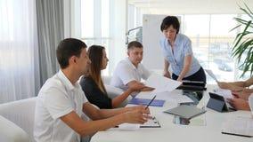 Mentore femminile con i documenti nelle mani che discute sviluppo di affari di idee con i collaboratori nell'ufficio stock footage