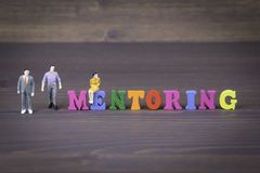 Mentoring. colored wooden letters on a dark background royalty free stock photos
