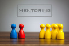 Mentoring concept with pawn figurines on table. Grey background royalty free stock images