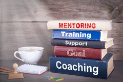 Mentoring concept. Stack of books on wooden desk Stock Photo