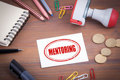 Mentoring stamp. Wooden office desk with stationery, money and a note pad Stock Image