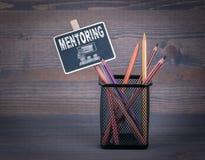 mentoring Una pequeña tiza de pizarra y un lápiz coloreado en el fondo de madera Fotografía de archivo libre de regalías
