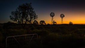 Mentre il sole aumenta, i mulini a vento dell'azienda agricola sono profilati sulla luce dorata fotografie stock libere da diritti