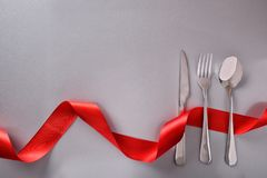 Menu background for restaurant with cutlery on gray table. Menu background for restaurant with silver cutlery and red ribbon on gray table background Royalty Free Stock Image
