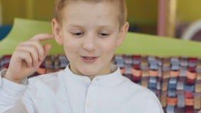 Menu beau, jeune et gai de lecture de garçon et pensée en café clips vidéos