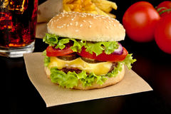 Menu- big cheeseburger with french fries and glass of cola on wooden black desk on black Royalty Free Stock Image
