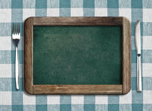 Menu blackboard lying on tablecloth Stock Image