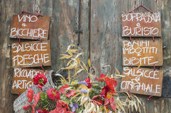 Menu on blackboards in Italy. Menu on wooden signs with basket of flowers, Arezzo, Tuscany, Italy Royalty Free Stock Photography