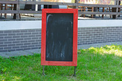 Menu blank board with a street cafe or restaurant in the background. Royalty Free Stock Photography
