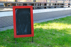 Menu blank board with a street cafe or restaurant in the background. Royalty Free Stock Photos