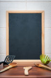 Menu board. Black board with cooking tools for writing the menu Stock Photography