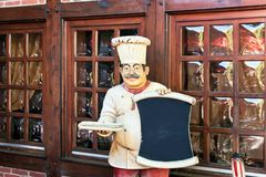 Menu board with statue. Of chef  outdoors Royalty Free Stock Photos