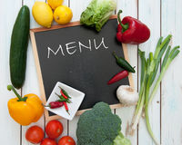 Menu. Board surrounded by fresh products and ingredients Royalty Free Stock Photography