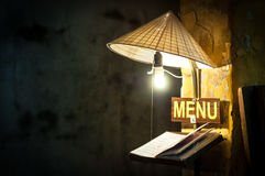 Menu in cafe under light of bulb in rice hat. Stock Photo
