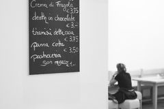 Menu in a cafe on the wall with women sitting on a Stock Photos
