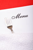 Menu card. Empty menu card with fork on red mat stock photo