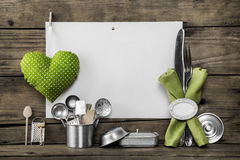 Menu card with old kitchen utensils, white placard, apple green. Doted heart, equipment and pots on an old nostalgic background Royalty Free Stock Image
