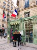 Menu Case Tea House Champs Élysées Paris. People reading a menu case of a Salon de Thé (Tea House) on the avenue des Champs Élysées, Paris, France. March 8 Stock Photography