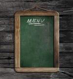 Menu chalkboard or blackboard in restaurant. On wooden wall Royalty Free Stock Images