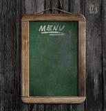 Menu chalkboard or blackboard in restaurant. On wooden wall Royalty Free Stock Image