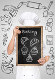 Menu chalkboard. Restaurant chef hiding behind a chalkboard with sketchy bakery sweets Royalty Free Stock Photos