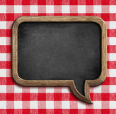 Menu chalkboard speech bubble on picnic tablecloth. Menu chalkboard speech bubble on table with picnic tablecloth Stock Images