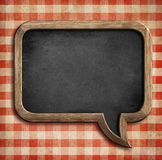 Menu chalkboard on table in shape of speech bubble Stock Photo