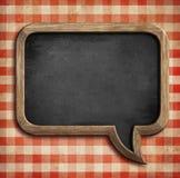 Menu chalkboard on table in shape of speech bubble. Speech bubble menu chalkboard on table Stock Photo