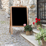 Menu chalkboard. Wooden board for restaurant menu with empty space to add text standing at restaurant entrance with flower pots Stock Image