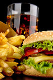 Menu of cheeseburger,french fries,glass of cola on black Stock Photography