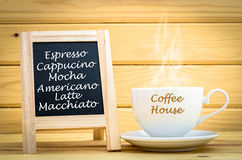 Menu coffee on black chalkboard with hot coffee in white cup and. Smoke in on wooden room Stock Photo