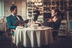 Menu da leitura dos pares em um restaurante foto de stock