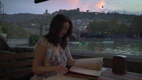 Menu da leitura da jovem mulher no café exterior em nivelar o tempo filme