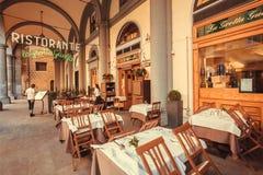 Menu da leitura da mulher do restaurante tradicional sob arcos da cidade antiga de Toscânia foto de stock
