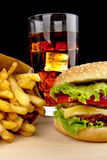 Menu de cheeseburger, pommes frites, verre de kola sur le bureau en bois sur le noir Photos libres de droits