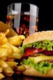 Menu de cheeseburger, pommes frites, verre de kola sur le noir Photographie stock