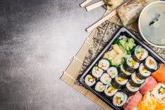 Menu dei sushi con i rotoli di estate, il nigiri, la salsa di soia e la minestra di miso su fondo di pietra grigio, vista superio fotografia stock
